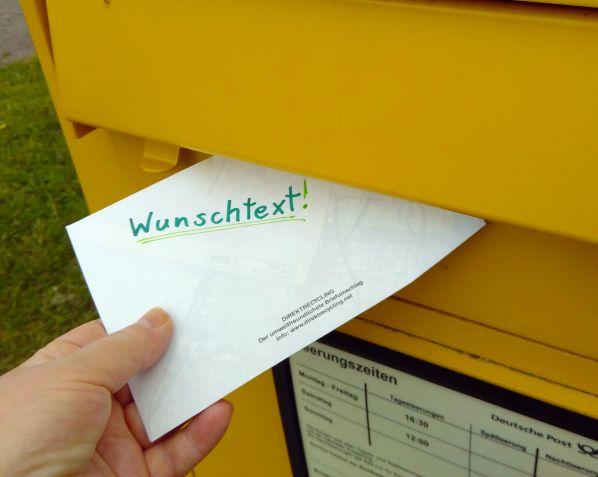 """Jemand steckt einen Briefumschlag mit der Aufschrift """"Wunschtext"""" ein einen gelben Briefkasten"""