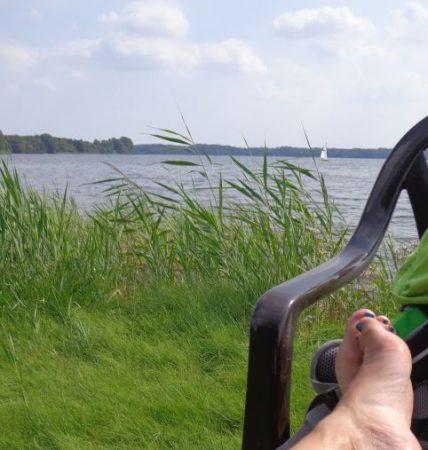 Wasser mit Segelboot in der Ferne, davor Schilf und im Vordergrund ein Paar Füße auf einem Stuhl