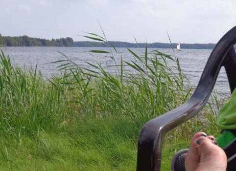 Wasser mit Segelboot in der Ferne, davor Schilf und im Vordergrund ein Paar Füße auf einem Stuhl.
