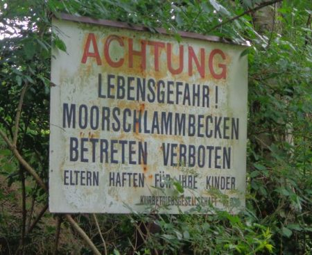 """Altes, überwachsenes Schild: """"Achtung. Lebensgefahr! Moorschlammbecken. Betreten verboten. Eltern haften für ihre Kinder"""""""